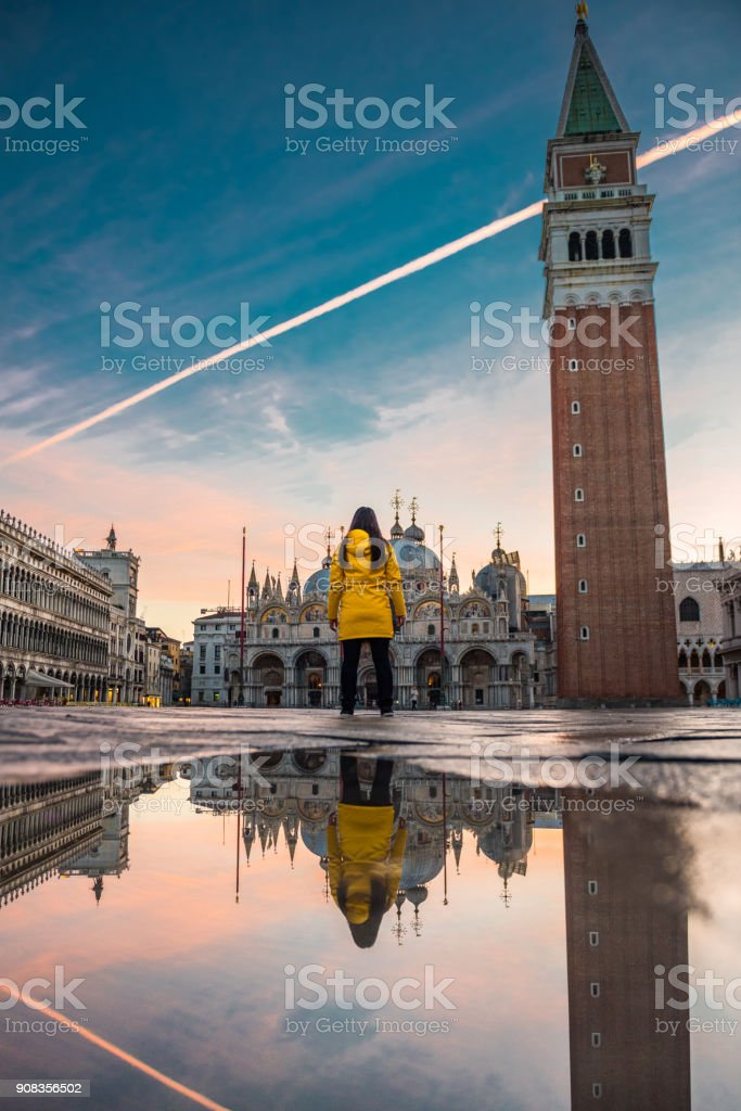 Young woman, in yellow raincoat seen from back at St. Mark square stock photo