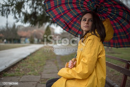 Young woman in yellow raincoat is waiting for someone in the park, sitting on the bench and holding opened umbrella. Rainy day in the city. Looking on left side.