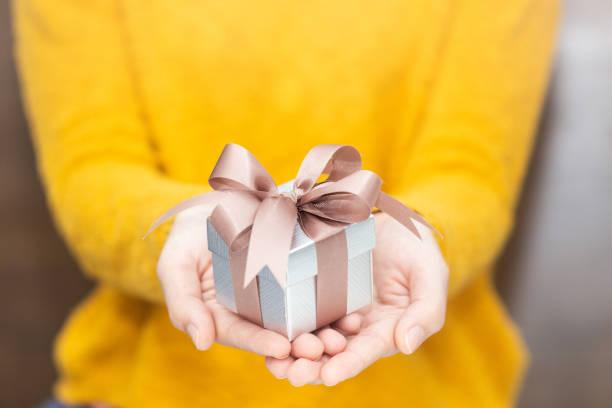 młoda kobieta w żółtym swetrze trzymająca pudełko na imprezę spacial. - gift zdjęcia i obrazy z banku zdjęć