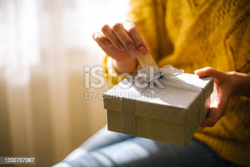 Young woman in yellow sweater opening gift box