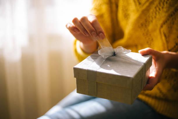 黄色のセーターの若い女性はギフトボックスを開きます - 誕生日の贈り物 ストックフォトと画像