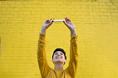 A 23 year old woman wearing yellow stands in front of a yellow brick wall. She is standing directly in front of the camera with her arms outstretched above her head to take a selfie with her smart phone. She is a member of the LGBTQI community and stands proud as a gender non conforming individual.