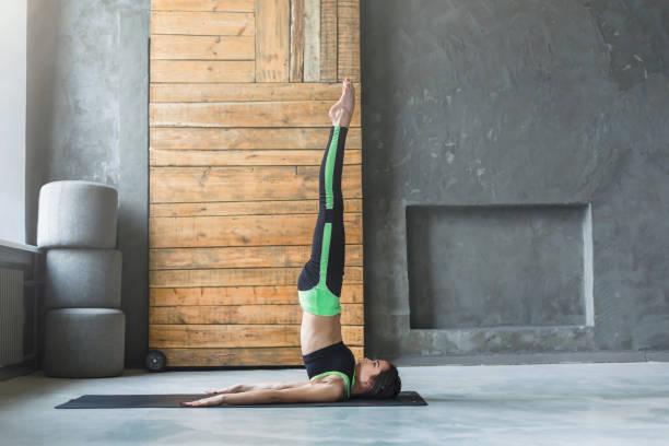 Young woman in yoga class doing shoulder stand Young woman in yoga class doing shoulder stand. Fit girl stretching in sarvangasana. Healthy lifestyle in fitness club, copy space on wall shoulder stand stock pictures, royalty-free photos & images