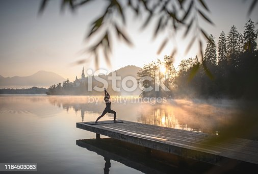 Mid distance view of young Caucasian woman standing on pier overlooking misty Lake Bled in yoga High Lunge Position (Utthita Ashwa Sanchalanasana) at dawn.