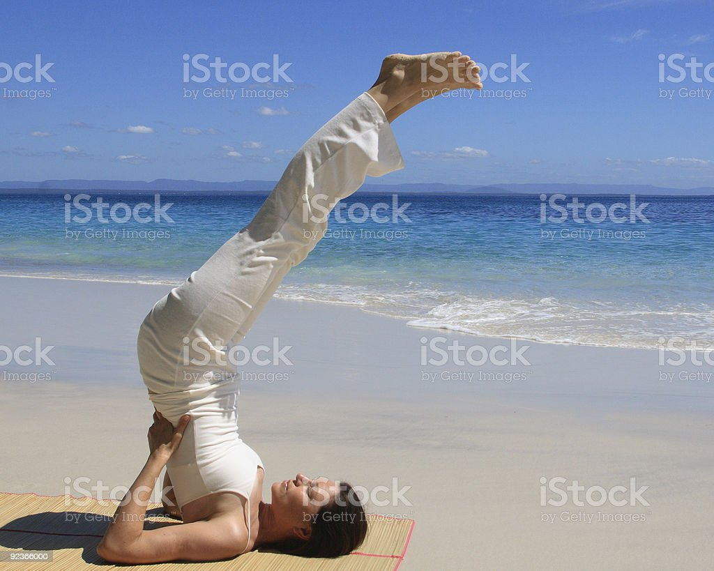 Young woman in Yoga pose on a beach stock photo