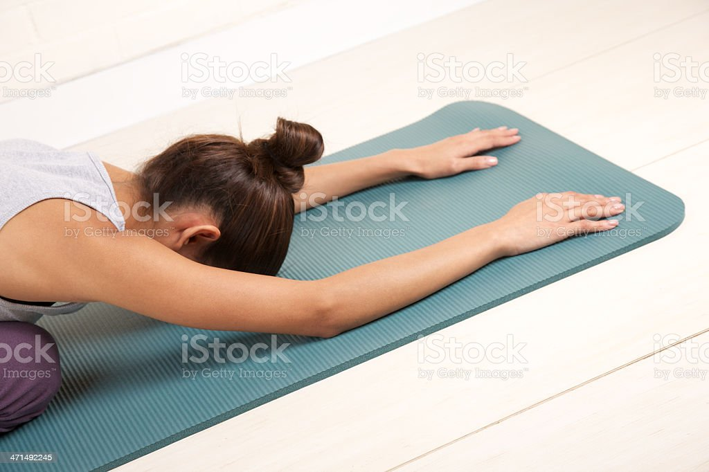 Young woman in yoga position called 'child's pose' royalty-free stock photo