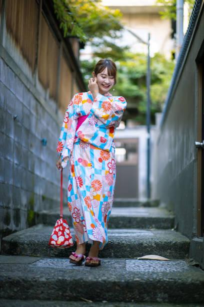 junge frau in yukata zu fuß treppe im traditionellen japanischen dorf - damenschuhe k stock-fotos und bilder