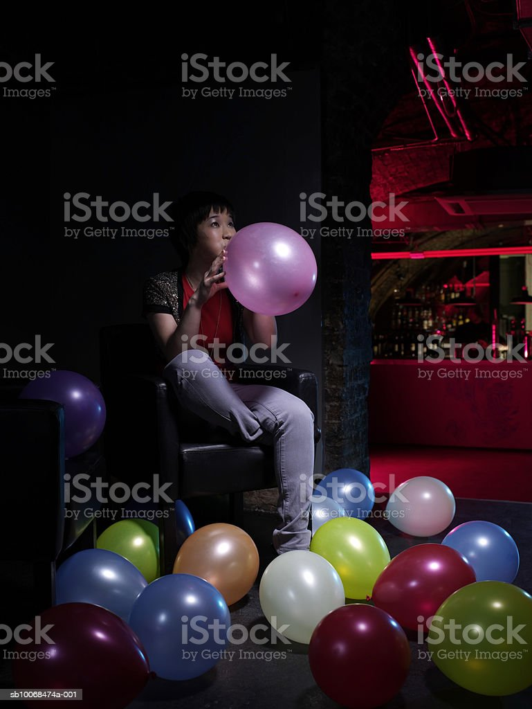 Jovem mulher inflating balões de festa foto royalty-free