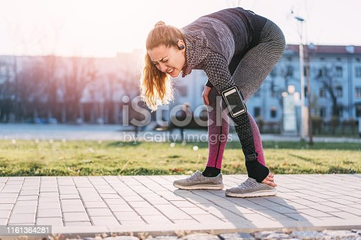 Beautiful young woman spraining her left ankle while training outdoors
