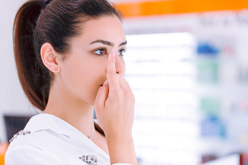 Beautiful young woman getting ready to insert contact lens