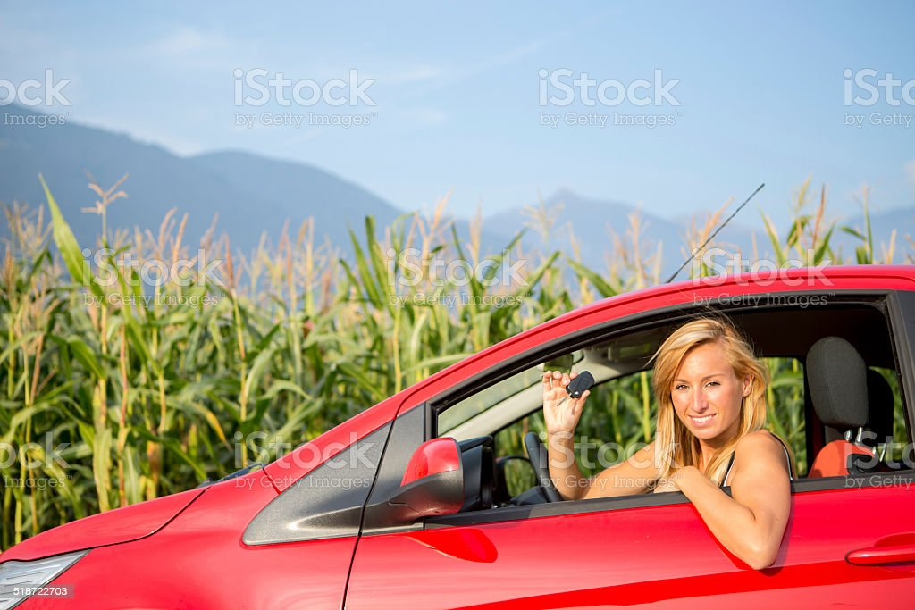 Young woman inside of a red car showing a key car.
