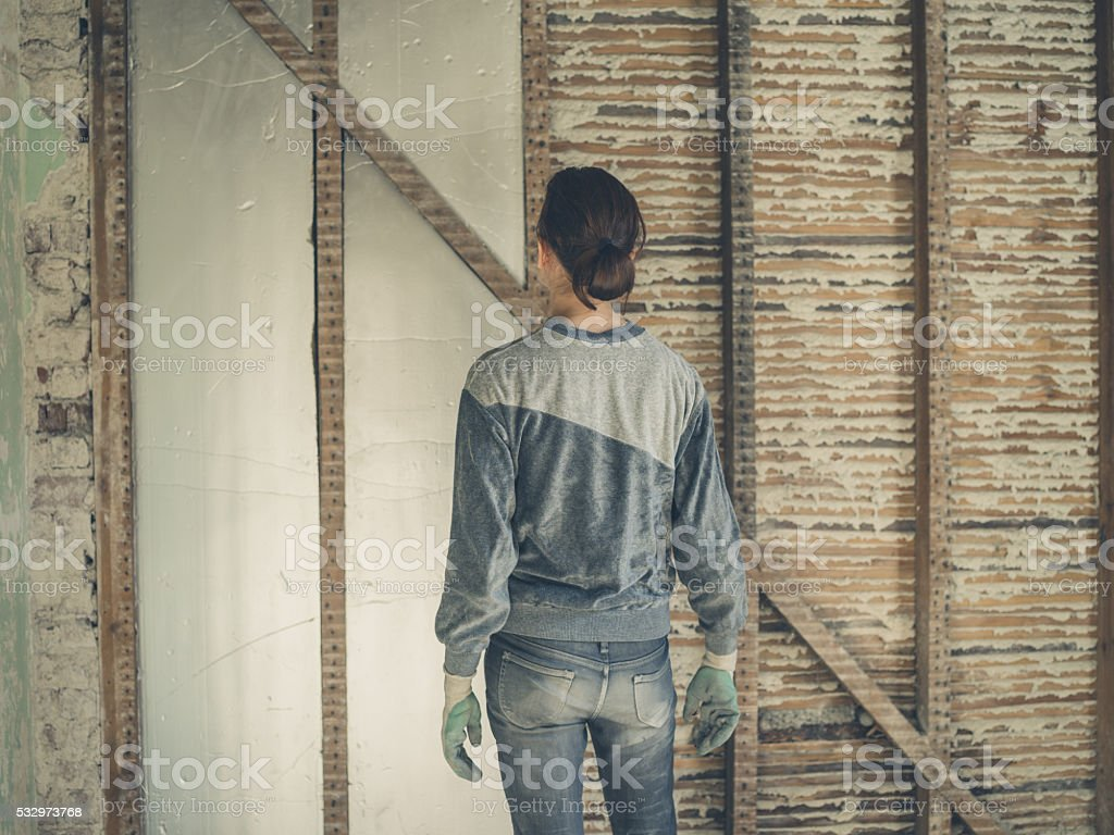Young woman insulating walls stock photo