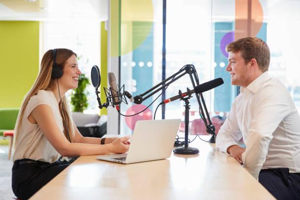 jonge vrouw interviewen een gast in een studio voor een podcast - podcast stockfoto's en -beelden