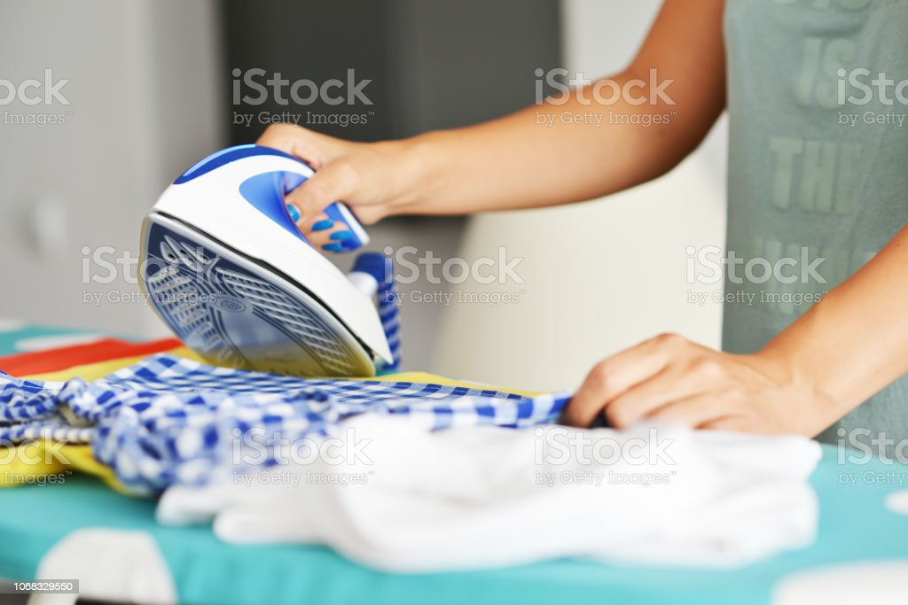 Young woman ironing kid's clothes with steam on ironing board stock photo