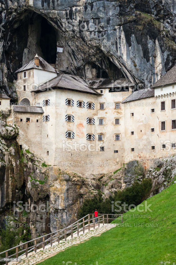 Young woman is admiring the magnificent Predjama Castle which is one of the most famous landmarks in Slovenia, attracting  thousands of tourists each year. stock photo