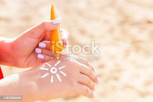 Young woman is applying sun cream on her hand in sun shape at the beach.