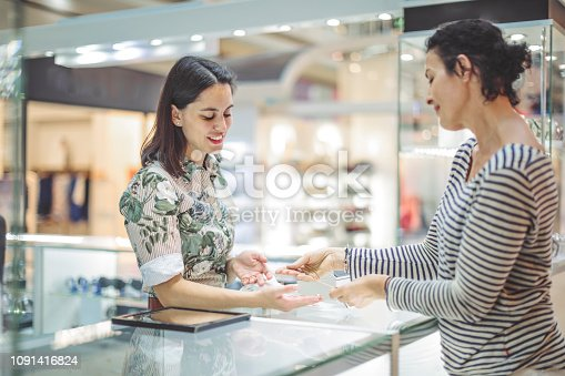 478253473istockphoto Young woman is buying a necklace at the shopping mall 1091416824