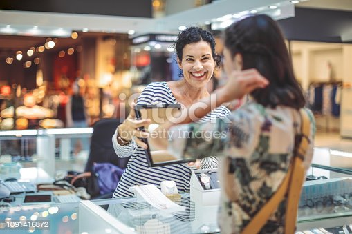 478253473istockphoto Young woman is buying a necklace at the shopping mall 1091416872