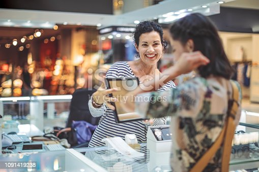 478253473istockphoto Young woman is buying a necklace at the shopping mall 1091419238
