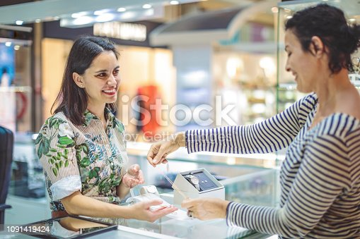 478253473istockphoto Young woman is buying a necklace at the shopping mall 1091419424