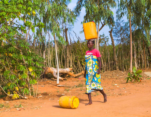 MALINDI, KENYA - January 24, 2017: A young woman is carrying water from a nearest hydrant to her home.