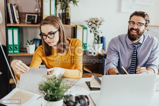 923634538 istock photo A young woman is choosing a color for the interior of the office 665910052