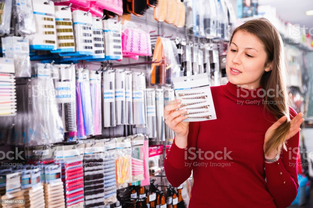 Young woman is choosing new hair clips in hair care store. royalty-free stock photo