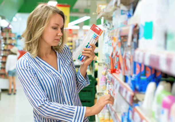 Young woman is choosing toothbrush in supermarket. stock photo