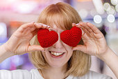 istock A young woman is closing her eyes with two hearts. 1087048052