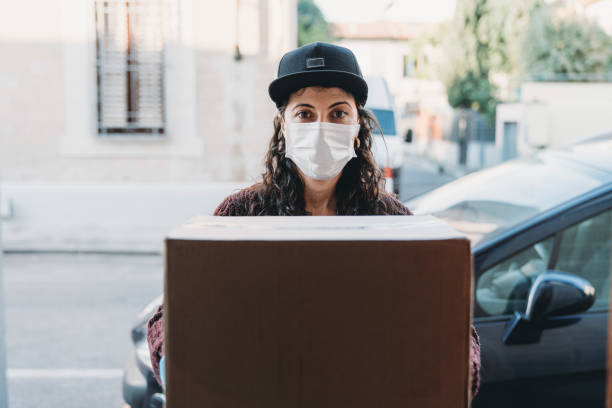 Young woman is delivering a cardboard box - View from inside the home stock photo