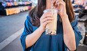 若い女性は、台湾、台湾珍味のナイト マーケットでストローでミルク バブルティーのプラスチック製のコップを飲んでいる、クローズ アップ。