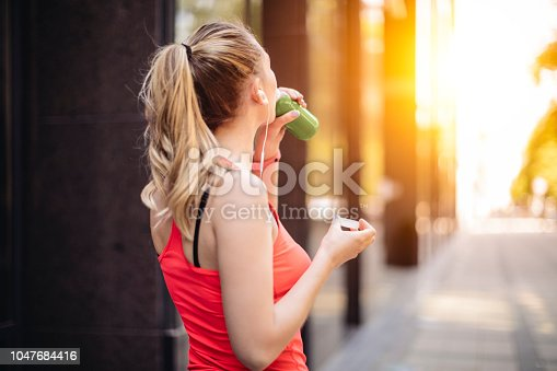 Young woman is drinking before exercising