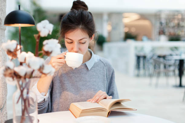 Young woman is drinking coffee and reading book under warm table lamp light. Girl is sitting in cozy modern cafe indoors. stock photo
