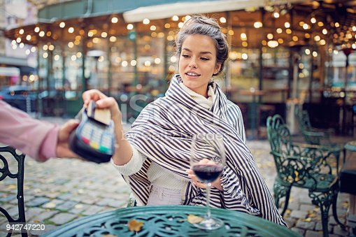 Young woman is drinking wine and paying with her contactless credit card