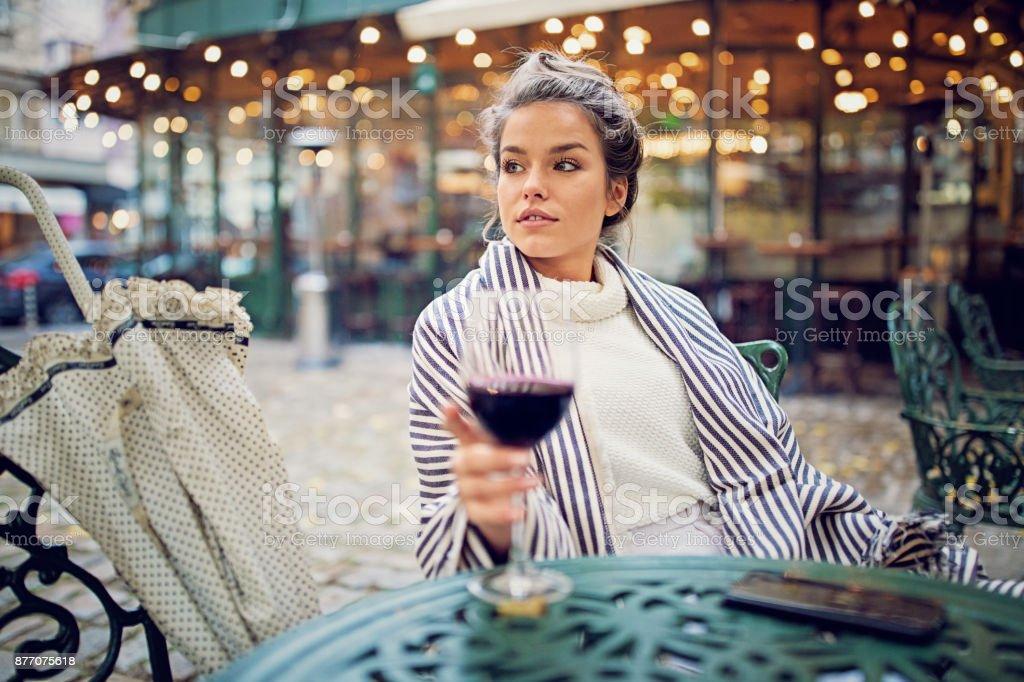 Junge Frau trinkt Wein an der Vorderseite der Cafeteria an einem regnerischen Tag – Foto