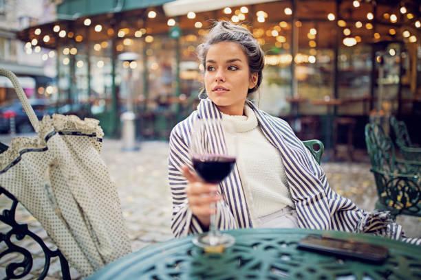 joven es beber vino en el frente de la cafetería en un día lluvioso - moda parisina fotografías e imágenes de stock