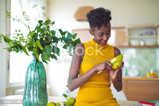 Young woman is eating a pear at home -