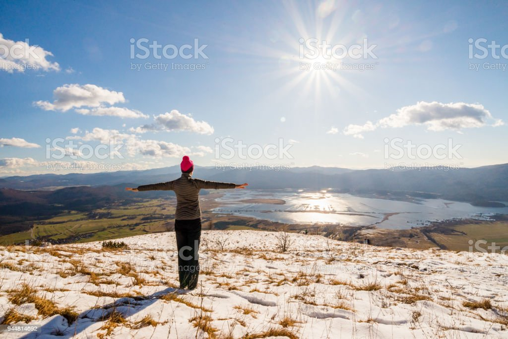Young woman is enjoying the view over Lake Cerknica on a sunny winter day in Slovenia. stock photo