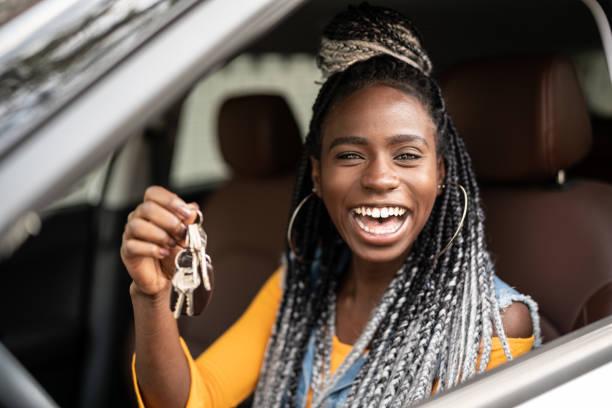 junge frau freut sich über neues auto - autos für fahranfänger stock-fotos und bilder