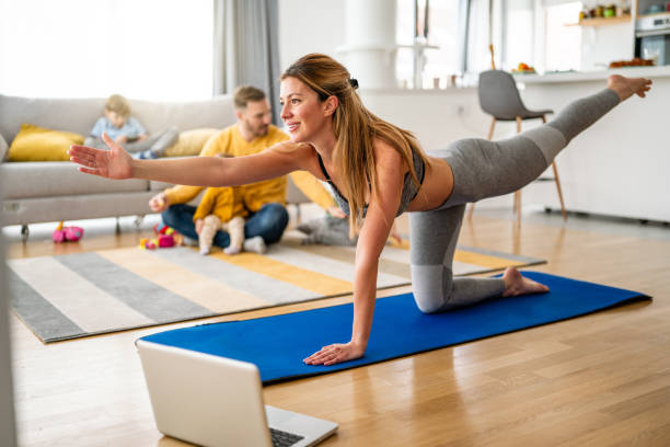 Young woman is exercising yoga at home. Fitness, workout, healthy living and diet concept. stock photo
