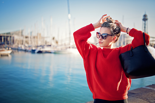 Young woman is fixing her hair on the yacht marina