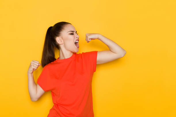 Young Woman Is Flexing Muscles And Shouting Beautiful young woman in orange shirt is flexing muscles and shouting. Waist up studio shot on yellow background. flexing muscles stock pictures, royalty-free photos & images