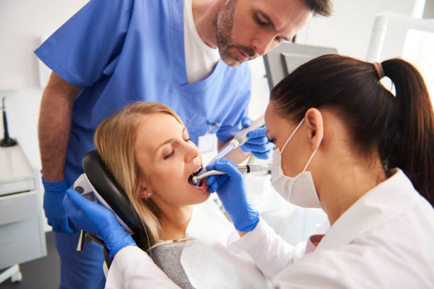 Young woman is getting treatment in dentist's office stock photo