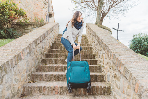 Young woman is going upstairs with her heavy luggage