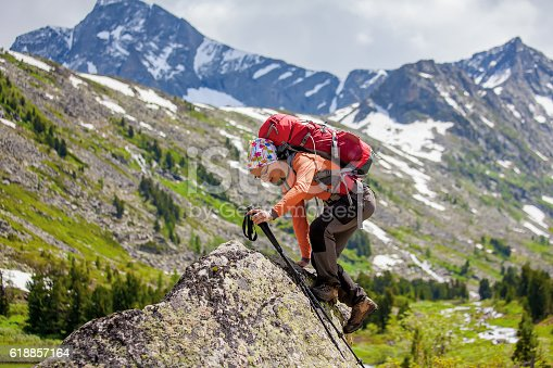 istock Young woman is hiking in highlands of Altai mountains, Russia 618857164