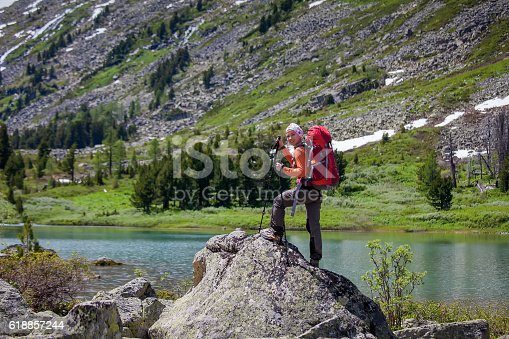 istock Young woman is hiking in highlands of Altai mountains, Russia 618857244