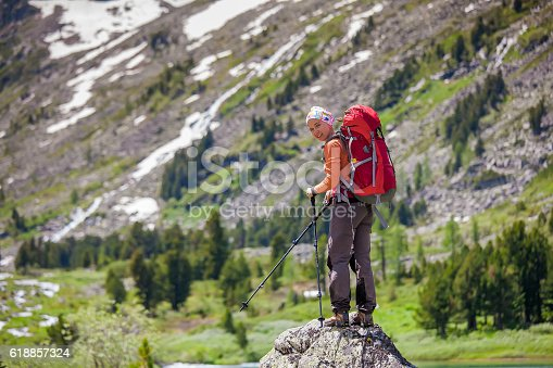 istock Young woman is hiking in highlands of Altai mountains, Russia 618857324