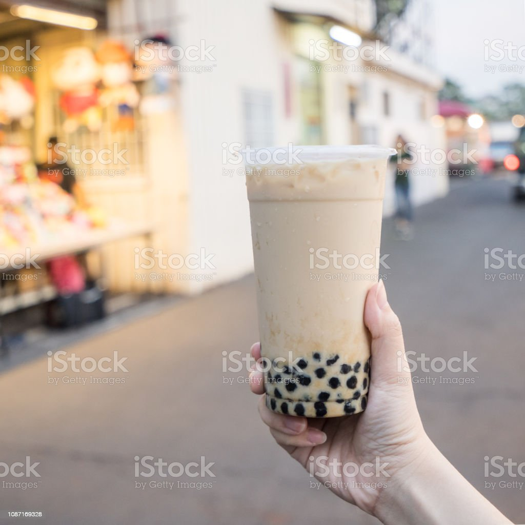 A young woman is holding a plastic cup of brown sugar bubble milk tea at a night market in Taiwan, Taiwan delicacy, close up. stock photo