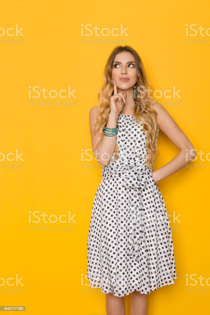 Young Woman Is Holding Finger In Chin, Looking Up And Thinking stock photo