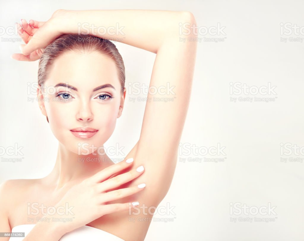 Young woman is holding her arm up and showing clean underarm. Cosmetology and armpit epilation. stock photo